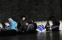 Pictured: Young families of migrants rest on the floor Monday 22 February 2016<br /> Re: Thousands of migrants, most from Syria, have landed to the port of Pireaus, after crossing the border from Turkey to various islands like Lesvos and Kos in Greece.