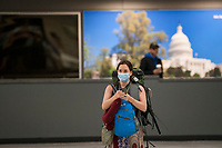 A woman wears a protective mask as she and other passengers arrive from Dubai after a 14-hour flight on Emirates flight 231, at the international terminal at Dulles International Airport in Dulles, Va., Monday, March16, 2020. Some people are taking the precaution of wearing face masks as they arrive to be greeted by family and or friends. Credit: Rod Lamkey / CNP/AdMedia