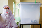 A female election official sits next to an almost empty ballot box at midday at a women's polling center in Kandahar, Afghanistan, Thursday, Aug. 20, 2009. Fear of Taliban attacks kept many women at home during Afghanistan's presidential and provincial council elections.