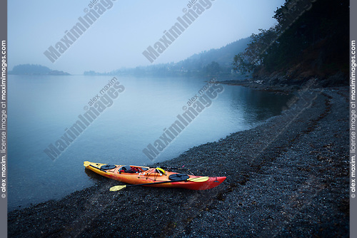 Red kayak on the Salish sea shore in yearly morning mist. Nanaimo, Vancouver Island, British Columbia, Canada. Image © MaximImages, License at https://www.maximimages.com
