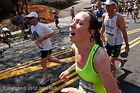 Cooled off with a sponge-full of ice water, a runner receives momentary relief from the hot sun & high temperatures on Heartbreak Hill during the 2012 Boston Marathon.