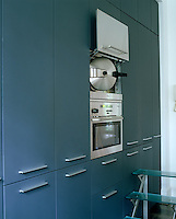 A wall of contemporary built-in cupboards encases this stainless steel oven with a separate wall-mounted steamer
