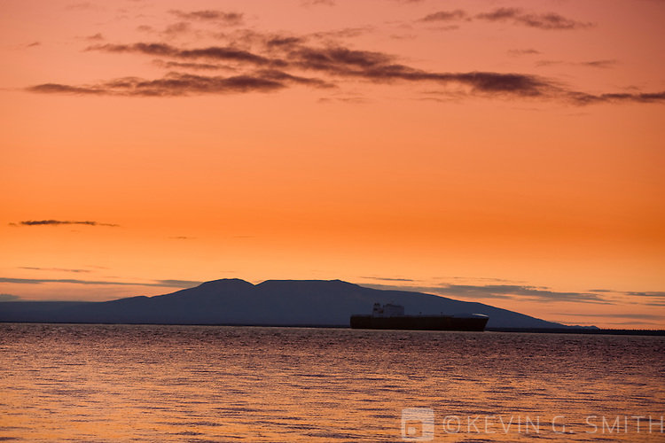 Cargo Ship sailing up Knik Arm towards the Port of Anchorage to unload, mount Susitna in the background, high tide, sunset, Anchorage, Scouthcentral Alaska, USA.