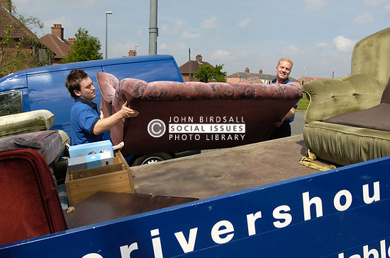 Housing Association staff throwing out old furniture from a house that is changing tenancy, NE England