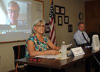 NWA Democrat-Gazette/ANDY SHUPE<br /> Jeanne Champagne (center), Robert Maranto (shown at left via projection from a remote location) and Phil Jones (right), all candidates for the Zone 2 seat on the Fayetteville Board of Education, participate Friday, Sept. 4, 2015, in a candidate forum at the Fayetteville Chamber of Commerce.
