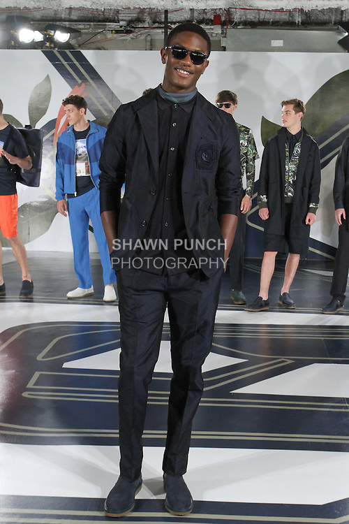 Model Hamid poses in a jacquard ultra-light suit in navy, and knit mesh shirt in navy, from the Perry Ellis Spring 2017 collection by Michael Maccari, on July 11th 2017, during New York Fashion Week Men's Spring Summer 2017.