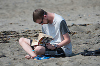 Aberystwyth Wales UK, Thursday 12 May 2016<br /> UK Weather: A man is reading the book 'Catastrophe' on the beach at the seaside in  Aberystwyth, on the Cardigan Bay coast of west Wales, enjoying a last day of warm weather in the current mini-heatwave. <br /> The temperatures are set to fall over the coming days, with bright but colder conditions prevailing over the country