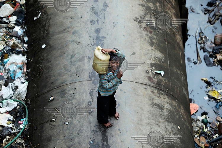 A boy is transporting water while standing on a water pipe in a dump in Dharavi. Dharavi is India's biggest slum and home to more than a million people. The water pipe provides water to more affluent areas of Mumbai. In Dharavi people have very limited access to piped water and where available the flow often runs for a few hours each day. Slum dwellers frequently suffer from diseases attributed to poor water and sanitation facilities.