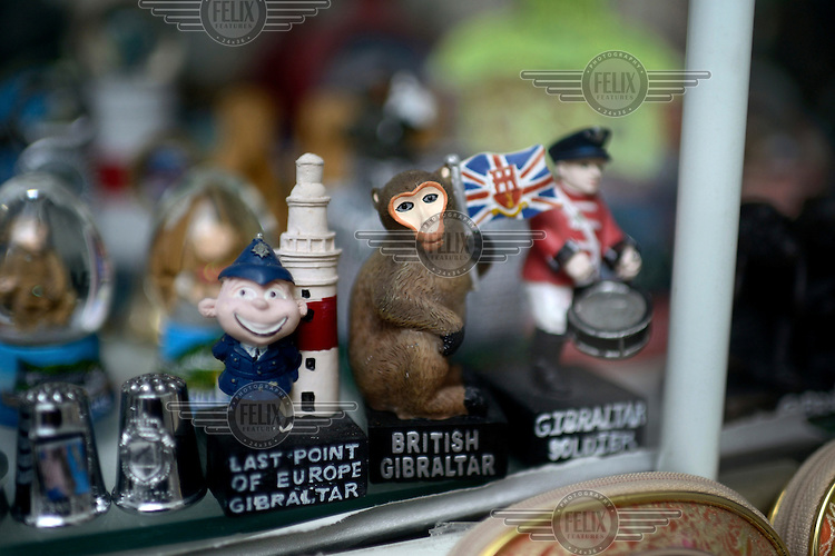 Tourist souvenirs, including a Barbary Macque and symbols of Gibraltar's Britishness, for sale in a shop window.