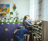 Zum Schutz vor Schüssen werden Sandsäcke in dem Gebäude verteilt. / Schule von Marinka im Donbass im ukrainisch kontrollierten Teil, 1,5 km von der Frontlinie. Die Schule wurde mehrmals beschossen. Seit dem Schulanfang am 01. September soll eigentlich eine Waffenruhe herrschen. Von ehemals 350 Kindern sind nur noch 160 an der Schule.