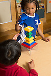 Preschool 4 year olds two boys building together with colored plastic stacking pieces