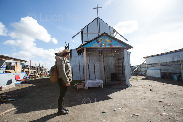"""The Church.<br /> <br /> Calais Jungle Camp.<br /> <br /> Under the Sky of Calais & Dunkirk. Two Camps, Two Sides of the Same Coin: Not 'migrants', Not 'refugees', just Humans.<br /> <br /> France, 24-30/03/2016. Documenting (and following) Zekra and her experience in the two French camps at the gate of the United Kingdom: Calais' """"Jungle"""" and Dunkirk's """"Grande-Synthe"""". Zekra lives in London but she is originally from Basra in Iraq. Zekra and her family had to flee Kuwait - where they moved for working reason - due to the """"Gulf War"""", and to the Western Countries' will to """"export Democracy in Iraq"""". Zekra is a self-motivated volunteer and founder of """"Happy Ravers"""", a group of people (not a NGO or a charity) linked to each other because of their love for rave parties but also men and women who meet up every week to help homeless people and other people in need in Central London. (Here there are some of the stories I covered about Zekra and """"Happy Ravers"""": http://bit.ly/1XVj1Cg & http://bit.ly/24kcGQz & http://bit.ly/1TY0dPO). Zekra worked as an English teacher in the adult school at Dunkirk's """"Grande-Synthe"""" camp and as a cultural mediator and Arabic translator for two medic teams in Calais' """"Jungle"""". Please read her story at the beginning of this reportage."""