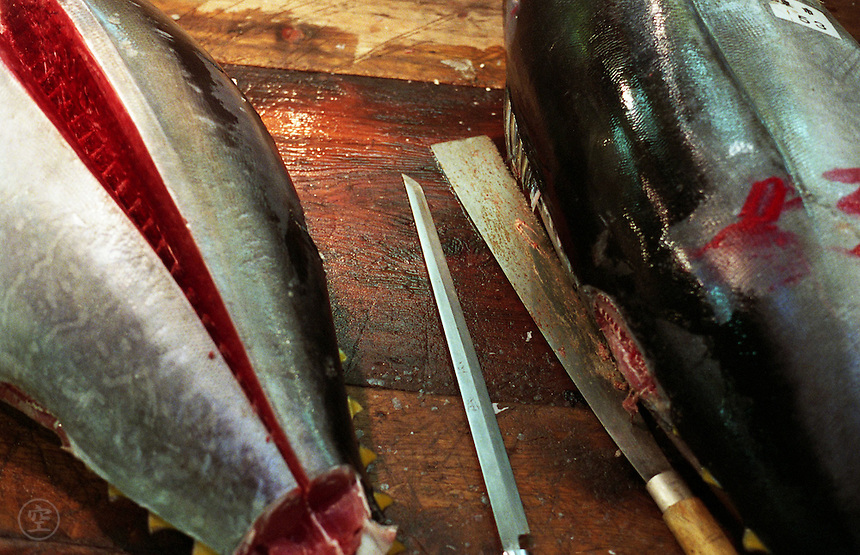 Knives for cutting whole tuna rest on a cutting board next to the fish themselves, Tsukiji Fish Market, Tokyo, Japan