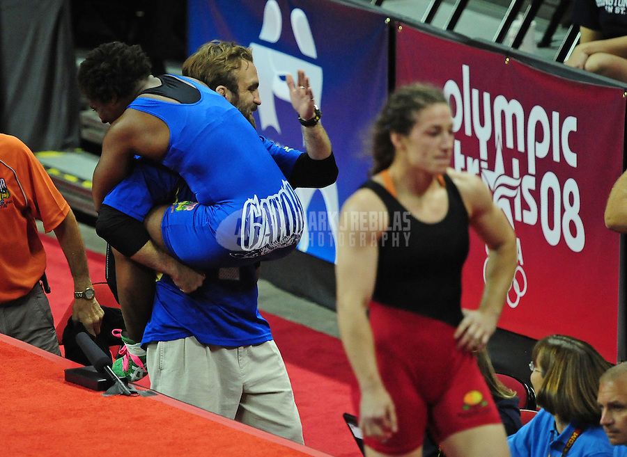 Jun 13, 2008; Las Vegas, NV, USA; Randi Miller (blue) celebrates with her caoch as a dejected Sara McMann walks by following the final in the womans 63kg class at the 2008 US Olympic Team Trials at the Thomas and Mack Center. Miler won the match and qualified for the Olympics. Mandatory Credit: Mark J. Rebilas-