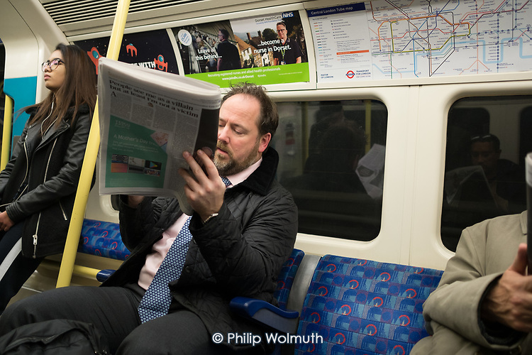 Man reading a newspaper on a London underground train.