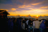Many tourists enjoying the sunrise at the visitor center atop the mountain at HALEAKALA NATIONAL PARK on Maui in Hawaii USA