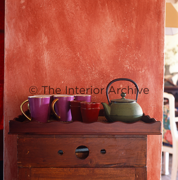 A tray with an iron teapot and bold coloured china designed by Ilaria Miani stands against a red stuccoed wall
