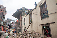 People collect items from their destroyed house in Shanku near Kathmandu, Nepal. May 9, 2015