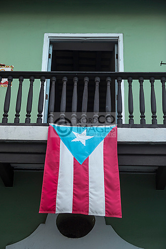 PUERTO RICAN FLAG DRAPED FROM BALCONY OF COLORFUL PAINTED BUILDINGS CALLE SAN SEBASTIAN OLD SAN JUAN PUERTO RICO