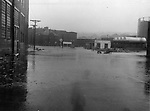 Bank Street at Meadow Street was more like a stream than a road yesterday as water from the rising Naugatuck River flooded the section with close to three feet of water. Ruins from the old Moose Hall, which was badly damaged in the August 19th flood, still lie on the ground beside the gas station. 16 October 1955.