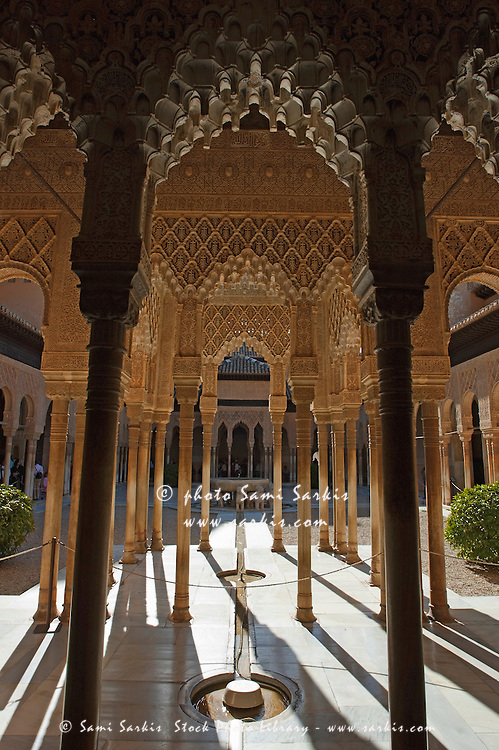 Tourists in the courtyard in the Patio de los Leones area at Alhambra, a 14th-century palace in Granada, Andalusia, Spain.
