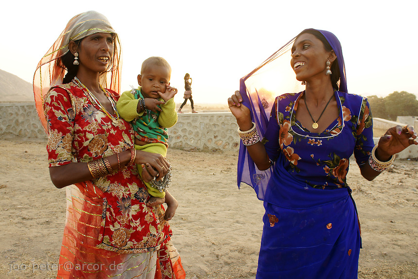 Babhu Dewi  in blue sari and her sister-in-law Kalassi with her baby chat at sunset time about camel fair business in holy city Pushkar. Babhu Dewi and her clan of the Bhopa cast (musicians)  is living in simple tents without electricity  in the desert. The Saris and jewlery they wear are basically all property they have.