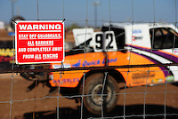 Apr 16, 2011; Surprise, AZ USA; LOORRS driver Jacob Person (92) jumps past a sign on the safety catch fence in front of the grandstands during round 3 at Speedworld Off Road Park. Mandatory Credit: Mark J. Rebilas-.