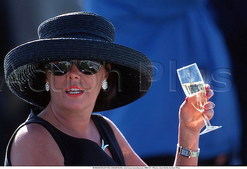 WOMAN ENJOYING CHAMPAGNE, Glorious Goodwood, 990727. Photo: Glyn Kirk/Action Plus...1999.horse racing.equestrian.hospitality.fashion.glamour.dress dresses.outfit outfits.hat hats.woman