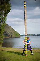 Neil Elliott wears a kilt as he holds a caber near his home in Dumbarton. He competes in over 40 Highland Games and heavyweight events across the world throughout the summer.
