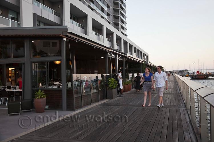 Couple walking along waterfront boardwalk at Harbour Lights.  Cairns, Queensland, Australia