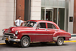 Havana, Cuba; a red, classic 1952 Chevy car, serving as a taxi, parked along the street in Havana