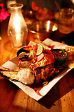 BELIZE, Caye Caulker, food shot of a pork chop topped with a stone crab claw
