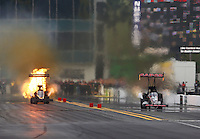Mar 14, 2015; Gainesville, FL, USA; NHRA top fuel driver Cory McClenathan (left) explodes an engine on fire alongside Steve Torrence during qualifying for the Gatornationals at Auto Plus Raceway at Gainesville. Mandatory Credit: Mark J. Rebilas-