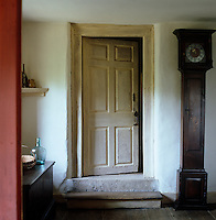 A grandfather clock in a plain case stands next to a rustic wooden door