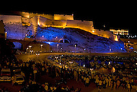 Crowd lining the streets surrounding Fort Saint-Nicholas illuminated at night with view of Pharo Palace in the distance, Marseille, France.