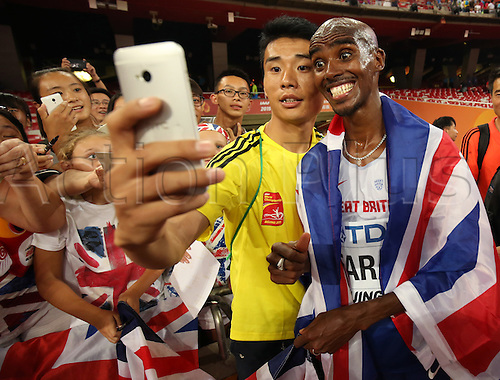 22.08,2015. Beijing, China.   Great Britain's Mohamed Farah celebrates with spectators and takes pictures after winning the Men's 10,000 M final at the 15th International Association of Athletics Federations (IAAF) Athletics World Championships at the National Stadium, known as Bird's Nest, in Beijing, China, 22 August 2015.