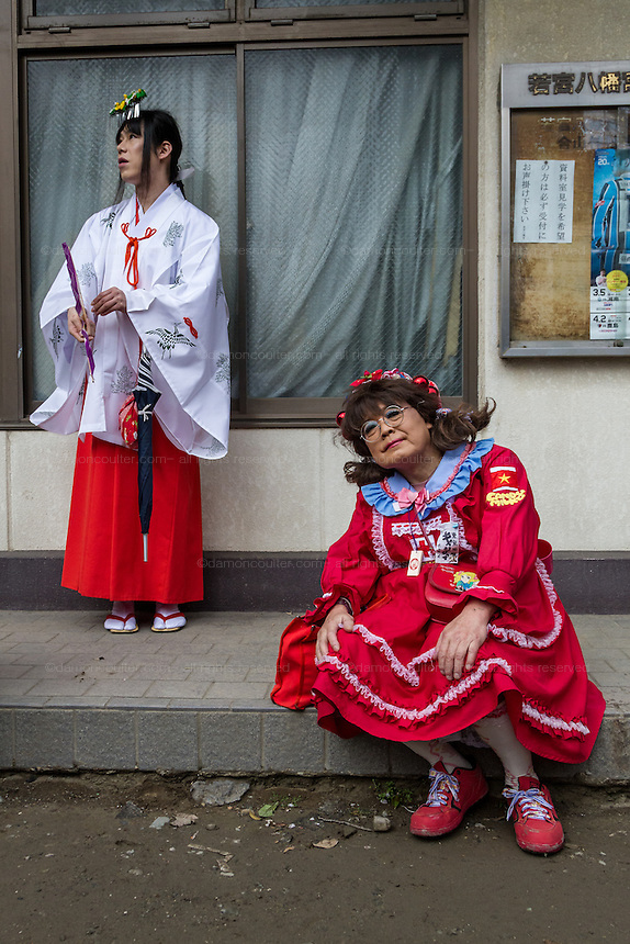 Two transvestites, one dressed as a little girl, the other as a Shrine maiden during the Kanamara Matsuri, (Festival of the Steel Phallus). Kawasaki Daishi, Kanagawa, Japan. Sunday April 3rd 2016. The famous Kawasaki Penis Festival started in 1977 as a small festival to celebrate an old legend about the defeat of a penis eating demon. Today the festival is a huge draw for Japanese and foreign tourists and raises money for HIV and AIDS research.