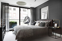 A stylish bedroom with a grey colour scheme. The double bed has a leather headboard and is dressed with cushions and a furry blanket. The room also has access to a balcony.