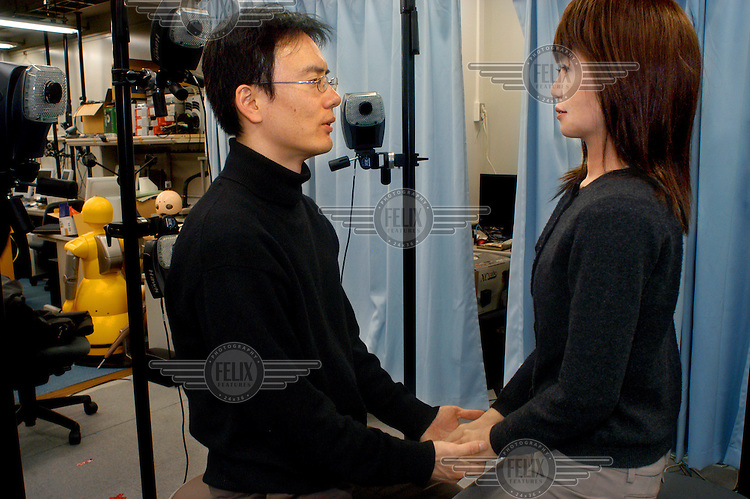 Minato Takashi, engineer and researcher at the University of Osaka, holds hands with Repliee Q2, a 'female' robot from 2004 inspired by a famous Japanese TV newsreader. ..