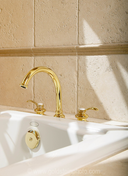 Bathtub detail showing gold faucet and tumbled stone tile.