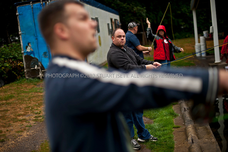 "9/17/2011--Orting, WA, USA..Ryan Garrett, 28, from Auburn, WASH.(foreground) and Guy Naylor, 42 (background), both army veterans, spend a day learning fly fishing at Bill's Fly Fishing Hole in Orting. WASH., about an hour's drive from Seattle. Both men are currently inpatients at the VA's hospital in Seattle suffering from Post Traumatic Stress Disorder (PTSD)...Healing Waters is a national nonprofit organization, founded to help disabled active-duty personnel and veterans by helping them, at no cost, to relearn fine motor skills and connect with other veterans, simply by learning the art of fly-fishing. It's an example of the kind of out-of-the-box thinking that is going into battling the devastating psychological effects of war. Some Healing Waters participants are in wheelchairs, missing limbs or just struggling with the transition to civilian life. Some suffer from PTSD, a condition that many say is like reliving hell. ..PTSD is an anxiety disorder brought on by a traumatic, life-threatening event. It is prevalent among combat veterans, but can also be experienced by civilians, including survivors of assault, rape, terrorist attacks, natural disasters and even extreme car accidents. Experts sometimes refer to it as the ""signature wound"" of our current conflicts in Iraq and Afghanistan, although statistics on the number of soldiers with PTSD remain vague. Studies report that it can occur in anywhere between 5 and 35 percent of soldiers returning from combat - or ""theater"" as it is referred to in the military. In 2010, 171,423 deployed Iraq and Afghanistan war veterans were diagnosed with PTSD, out of 593,634 patients treated by the VA--nearly one-third of them. And it's likely that diagnoses will continue to increase due to current soldiers experiencing multiple deployments--and thus, potentially longer exposure to trauma....©2011 Stuart Isett. All rights reserved."