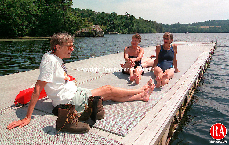 MIDDLEBURY, CT 08/04/98 --0804jh03.TIF--Some of the participants in a mini triathlon to raise funds for the purchase of the Whittemore Sanctuary took a break on the dock at the Middlebury Swim Club after their swim in Lake Quassapaug in Middlebury Tuesday. From left are Elaine Luckey of Washington, Ellen Torrance of Southbury, and Diana Wylie of Boston (formerly Woodbury). JOHN HARVEY staff photo for Wiley story.