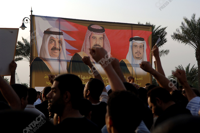 An opposition march protesting against alleged torture by Bahraini security forces and also amnesty for government officials who served before 2002 walked past a billboard with the portraits of the King, Crown Prince and Prime Minister of the country from the ruling al Khalifa family, December 17, 2005.