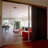Sliding doors open from the entrance hall into the living area where a pair of leather and chrome Marcel Breuer, Wassily chairs have been arranged around a coffee table with a pair of matching sofas upholstered in red