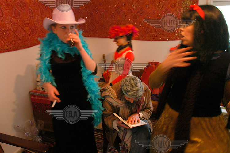 Women in fancy dress gather around a Jewish settler reading religious verses during a Purim holiday party in the Jewish settlement of Elazar.