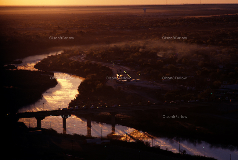 Morning fog rises at the World Trade Crossing over the Rio Grande River, the most important truck crossing on the United States/Mexican border. Texas border crossings account for most all truck traffic and the Laredo crossing alone represents over 60% of that traffic.