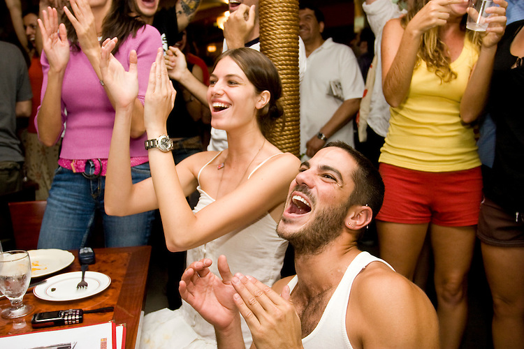 Spain fans Yosua Barea and Nuria de la Fuente cheer on their team during a World Cup match against Tunisia on June 19, 2006 at La Nacional, a restaurant in New York City.<br /> <br /> The World Cup, held every four years in different locales, is the world's pre-eminent sports tournament in the world's most popular sport, soccer (or football, as most of the world calls it).  Qualification for the World Cup is open to any country with a national team accredited by FIFA, world soccer's governing body. The first World Cup, organized by FIFA in response to the popularity of the first Olympic Games' soccer tournaments, was held in 1930 in Uruguay and was participated in by 13 nations.    <br /> <br /> As of 2010 there are 208 such teams.  The final field of the World Cup is narrowed down to 32 national teams in the three years preceding the tournament, with each region of the world allotted a specific number of spots.  <br /> <br /> The World Cup is the most widely regularly watched event in the world, with soccer teams being a source of national pride.  In most nations, the whole country is at a standstill when their team is playing in the tournament, everyone's eyes glued to their televisions or their ears to the radio, to see if their team will prevail.  While the United States in general is a conspicuous exception to the grip of World Cup fever there is one city that is a rather large exception to that rule.  In New York City, the most diverse city in a nation of immigrants, the melting pot that is America is on full display as fans of all nations gather in all possible venues to watch their teams and celebrate where they have come from.