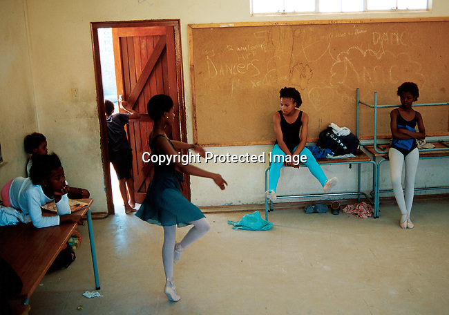 """Noluyanda Mqutwana, age 14, (center) warming up for a ballet class on June 10. 2000 in Yomelela school class room in Khayelitsha a poor township outside Cape Town , South Africa. About 200 kids from 6-18 are training dance in the """"Dance for all Programme"""" who was started by the Cape Town City Ballet to find talent in the townships..Photo: Per-Anders Pettersson (ppettersso@aol.com)"""