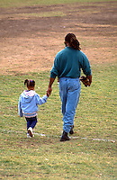 Father and daughter walking hand in hand off baseball field age 30 and 4. Brackett Field St Paul  Minnesota USA