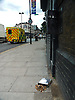 Cigarette end wall container spilt out on the pavement on a London street as an ambulance goes by.<br /> <br /> Stock Photo by Paddy Bergin